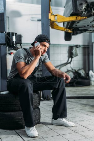 manual worker talking on smartphone and holding wrench in mechanic shop