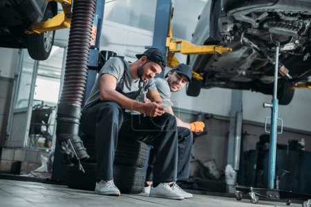 two auto mechanics using smartphone and resting in auto repair shop