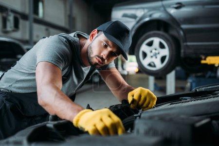 Photo pour Mécanicien professionnel en uniforme réparation de voiture en atelier - image libre de droit