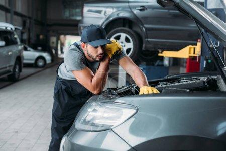 workman in uniform repairing car in mechanic shop
