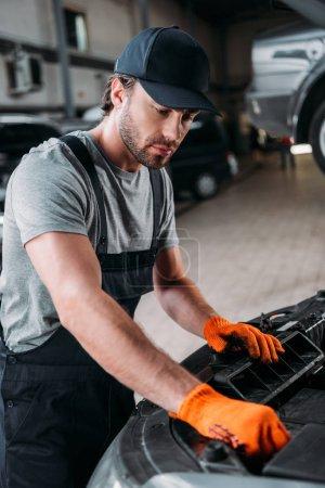 professional manual worker repairing car in mechanic shop