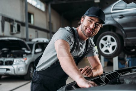 smiling auto mechanic working with car in repair shop