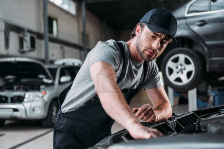 professional auto mechanic working with car in repair shop