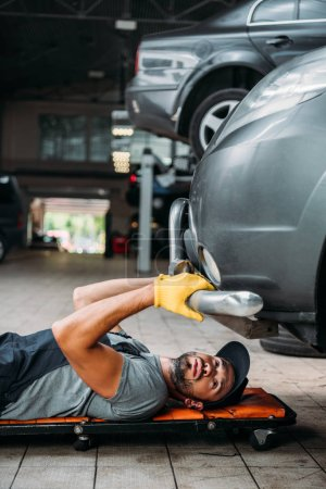 workman lying and working under car in mechanic shop