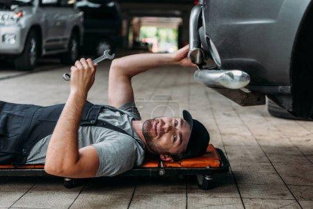 Photo pour Mécanicien couché et travaillant sous la voiture dans l'atelier de réparation automobile - image libre de droit