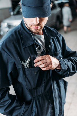 workman in cap and overalls holding tools in pocket