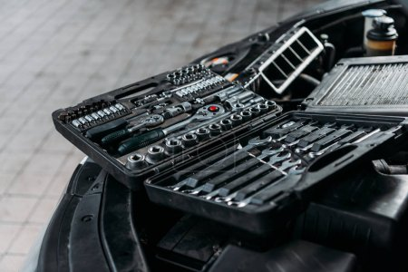 tool case with wrenches and metal nuts lying on opened car hood in workshop