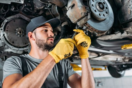 professional mechanic in uniform repairing car without wheel in workshop