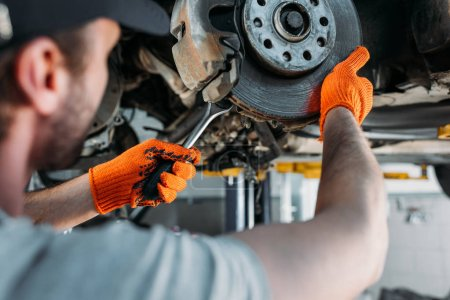 selective focus of professional worker repairing car without wheel in mechanic shop