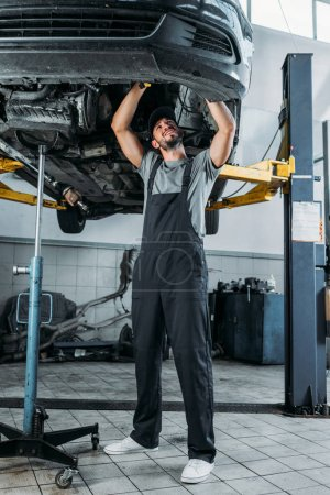 professional worker in uniform repairing a car in mechanic shop