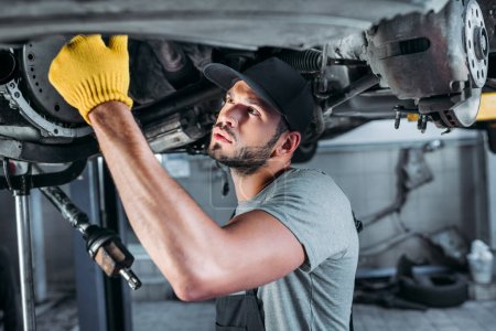 male mechanic fixing a car in auto repair shop