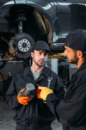 manual workers repairing car with tools in mechanic workshop