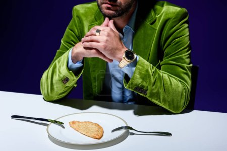 cropped shot of man in stylish green velvet jacket sitting at table with cheburek on plate with blue background behind
