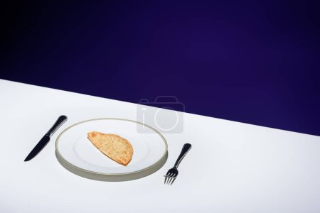 close up view of unhealthy meat pastry on plate and cutlery on table on blue background