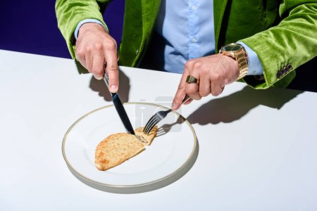 cropped shot of man in stylish green velvet jacket cutting meat pastry on plate with blue background behind