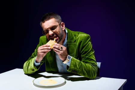portrait of man in stylish green velvet jacket eating meat pastry at table with blue background behind