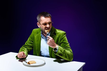 portrait of man in stylish green velvet jacket eating meat pastry on plate at table with blue background behind