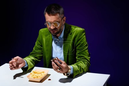 portrait of man in fashionable clothing sitting at table with french fries and ketchup with blue backdrop