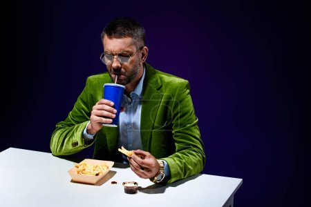 fashionable man in velvet jacket drinking soda drink while sitting at table with junk food with blue backdrop