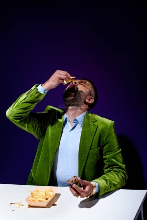 portrait of stylish man in green velvet jacket eating french fries with ketchup at table with blue background