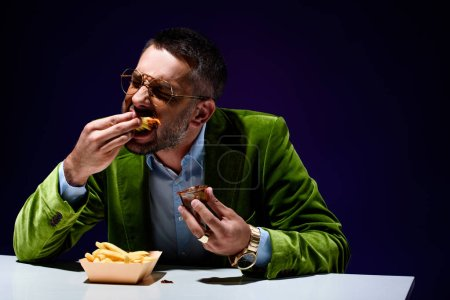 stylish man in velvet jacket eating french fries with ketchup at table with blue background