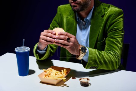 cropped shot of man in velvet jacket eating burger at table with french cries and soda drink with blue background