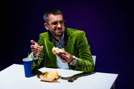 man in velvet jacket eating burger at table with french cries and soda drink with blue background