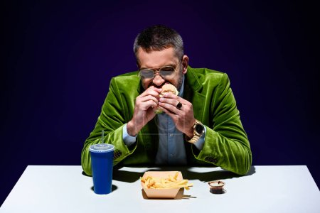 portrait of man in velvet jacket eating burger at table with french cries and soda drink with blue background