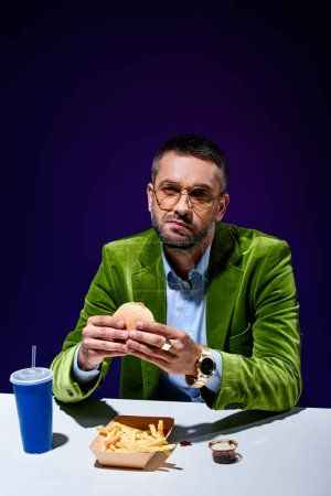 Photo for Man in velvet jacket eating burger at table with french cries and soda drink with blue background - Royalty Free Image
