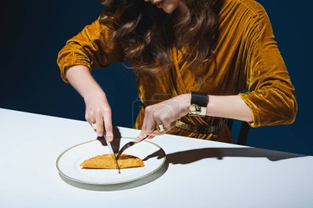 cropped shot of woman in stylish clothing cutting unhealthy meat pastry at table with blue backdrop behind