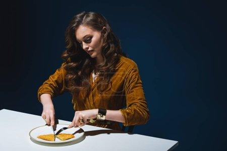 woman in stylish clothing cutting unhealthy cheburek at table with blue backdrop behind
