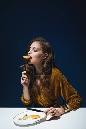 beautiful woman in stylish clothes eating meat pastry at table with blue background