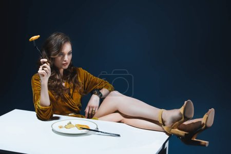 stylish woman with meat pastry on fork sitting at table with blue backdrop behind