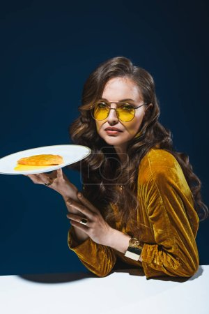 portrait of beautiful woman in stylish clothing with unhealthy cheburek on plate sitting at table with blue background behind