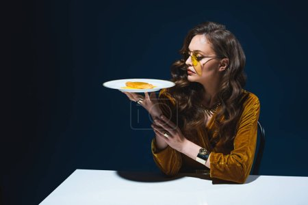 Photo for Beautiful woman in stylish clothing with unhealthy meat pastry on plate sitting at table with blue background behind - Royalty Free Image