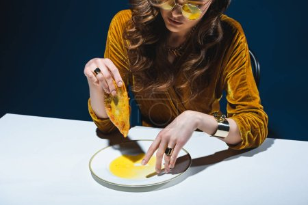 fashionable woman with unhealthy meat pastry sitting at table with blue backdrop