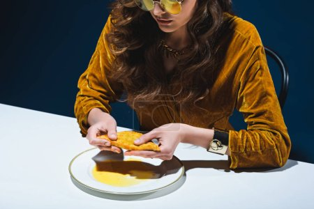 partial view of fashionable woman with unhealthy meat pastry sitting at table with blue backdrop