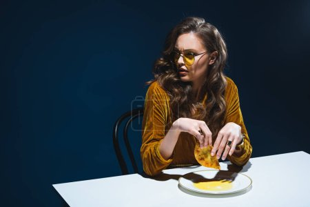 Photo for Fashionable woman with unhealthy meat pastry sitting at table with blue backdrop - Royalty Free Image