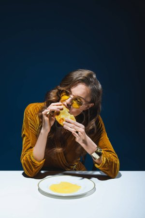 portrait of beautiful woman in stylish clothes eating meat pastry at table with blue background