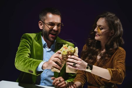 portrait of smiling couple in luxury velvet clothing with shawarma sitting at table with dark background behind