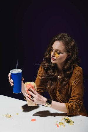 portrait of attractive woman in fashionable clothing with soda drink and shawarma sitting at table with blue backdrop