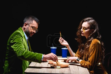 side view of couple in stylish velvet clothing sitting at table with fried onion rings, french fries and sauces with black background