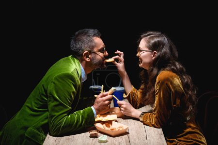 side view of couple in stylish velvet eating fried onion rings, french fries and sauces at table with black background