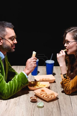 side view of couple in stylish velvet clothing eating fried onion rings, french fries and sauces at table with black background