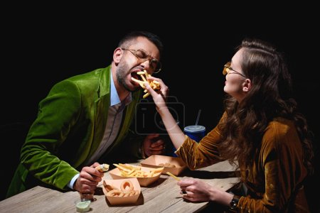 side view of couple in stylish velvet clothing eating french fries, fried onion rings and sauces at table with black background