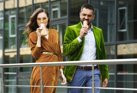 portrait of couple in luxury outfit eating french hot dogs while walking on street