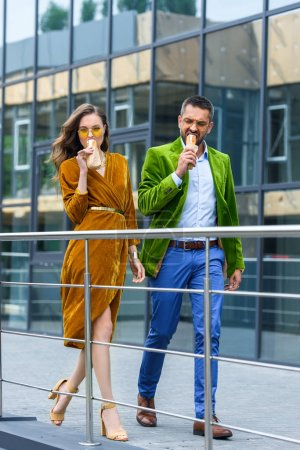 couple in luxury outfit eating french hot dogs while walking on street