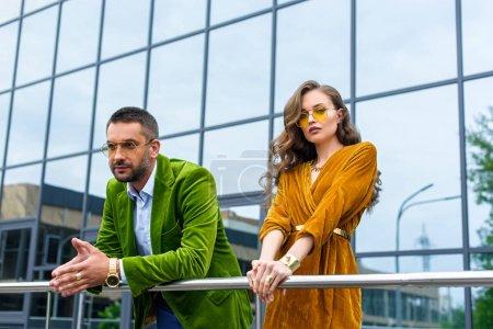 Photo pour Portrait de couple attractif en mode vêtements debout sur la rue et regardant la caméra - image libre de droit