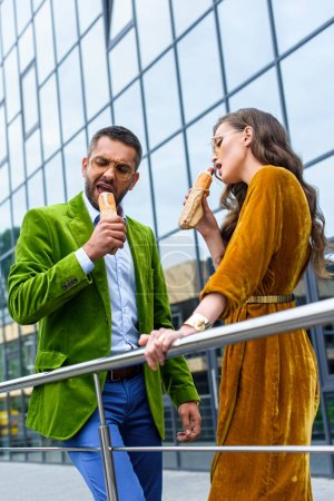 couple in luxury outfit eating french hot dogs on street