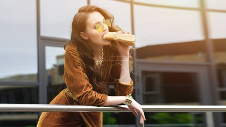 portrait of attractive woman in luxury clothing and sunglasses eating french hot dog on street